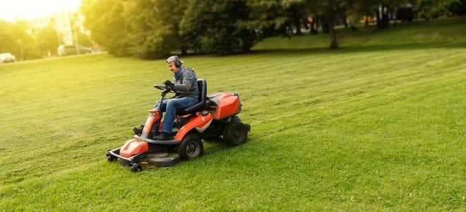 Man riding tondeuse à gazon dans une grande pelouse